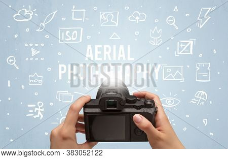 Hand taking picture with digital camera and AERIAL PHOTOGRAPHY inscription, camera settings concept