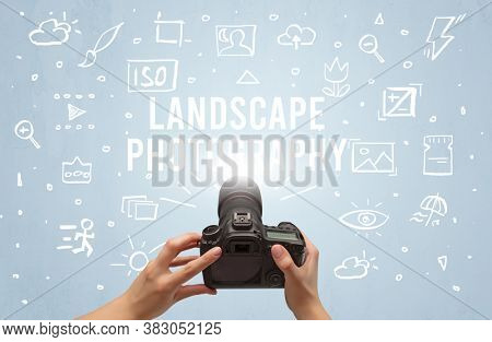Hand taking picture with digital camera and LANDSCAPE PHOTOGRAPHY inscription, camera settings concept