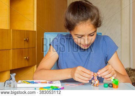 A Pretty Girl Sits At The Table At Home And Does Her Favorite Pastime, Sculpts From Plasticine.
