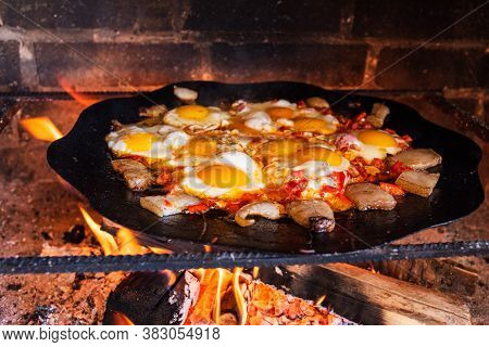 Eggs Are Fried On A Fire In The Street. Fried Eggs With Bacon. A Dish Of Many Fried Eggs On A Bonfir