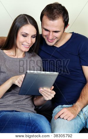 Couple using a tablet computer in their living room