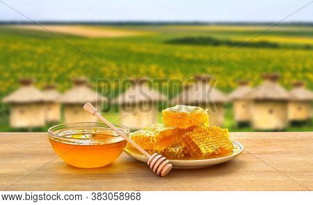 Honey In Glass Bowl, Wooden Honey Dipper And Honeycombs With Honey On Wooden Table On Background Of