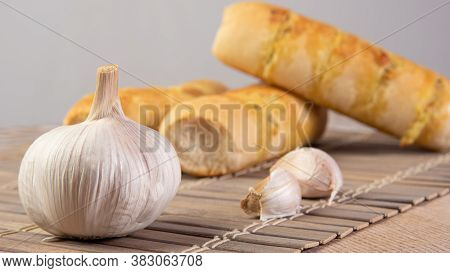 Garlic Bread Stuffed With Cheese Arranged On A Bamboo Mat With Garlic Around It On A Table, Selectiv