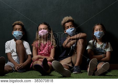 Four Multinational Children Wears Surgical Protective Cloth Facemasks School Age Girls And Boys Look