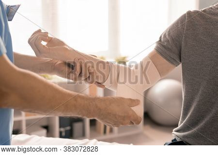 Hands of male clinician wrapping right elbow of sick young patient with flexible bandage during medical procedure in modern clinics