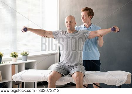 Young physiotherapist standing behind bald mature male patient with dumbbells outstretching arms while helping him with exercising