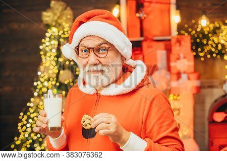 Santa Claus Enjoys Cookies And Milk Left Out For Him On Christmas Eve. Cheerful Santa Claus Holding