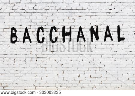 White Brick Wall With Inscription Bacchanal Handwritten With Black Paint