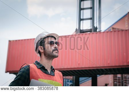 Portrait Of Confident Transport Engineer Man In Safety Equipment Standing In Container Ship Yard. Tr