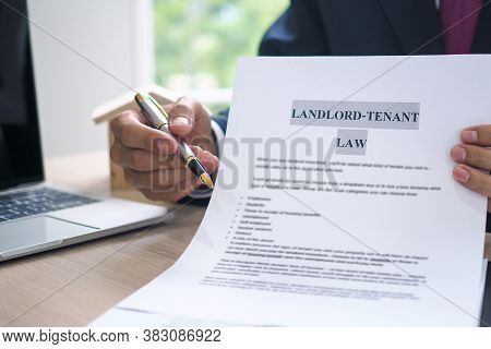 The Hand Of A Man Holding A House Purchase Contract With A Pen Showing Up To Customers. House Salesm