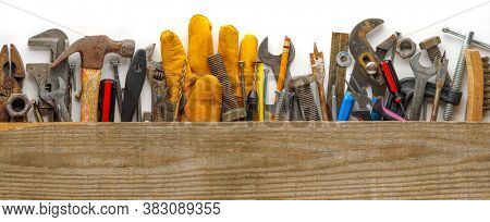 Worn wood plank on used and dirty work tools for home improvement or diy repair projects. Includes wrench, work gloves, hammer, measuring tape, screwdriver, pliers, and other tools.