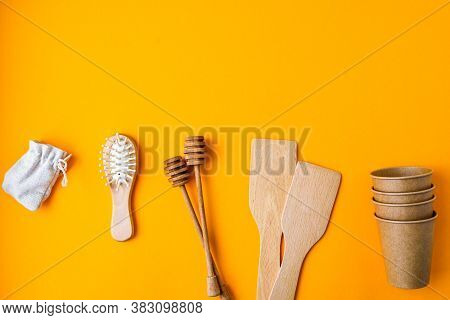 Eco Friendly Disposable Paper Cups, Wooden Kitchen Tools, Hairbrush Cotton Bag On Yellow Background.