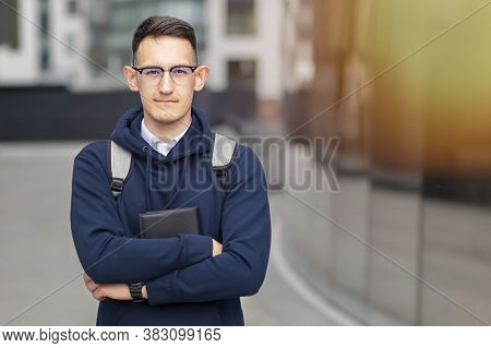 Portrait Of Handsome Young Guy, University Or College Student With Book, Backpack And Glasses Outdoo