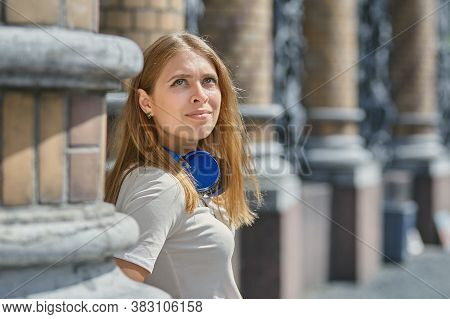 Blonde Young Woman Walks Outdoors. Caucasian Beautiful Pensive Female About 25 Years Old With Blond