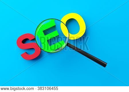 Magnifying Glass Or Loupe Enlarging The Word Seo, Search Engine Optimization, Over Blue Background,