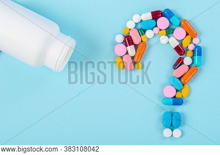 A Question Mark From Laid Out Of Medicine Pills With Bottle Drug On Blue Background.