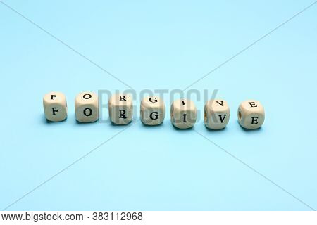 Cubes With Word Forgive On Color Background