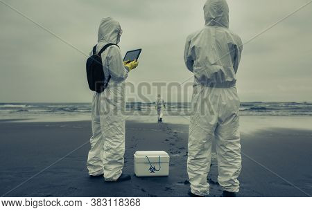 Unrecognizable People With Bacteriological Protection Suits Looking For Evidence At Sea