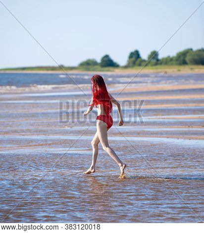 Beautiful Redhead Young Woman In Red Transparent Swimsuit