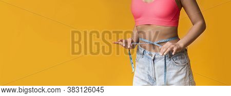 Weightloss Concept. Slim Unrecognizable Woman Measures Her Waist With Measuring Tape, Standing Over