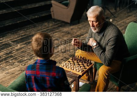 Top View Of Aged-male Grandfather Playing Chess With Grandson Sitting At Desk In Cozy Dark Living Ro