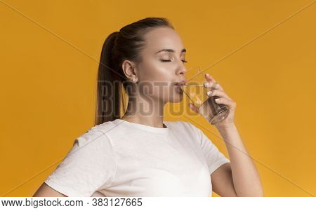 Hydration Concept. Young Woman Drinking Mineral Water, Enjoying Healthy Drink, Standing Over Yellow