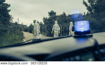 View From Emergency Car Of People With Bacteriological Protection Suits Walking On A Road Looking Fo