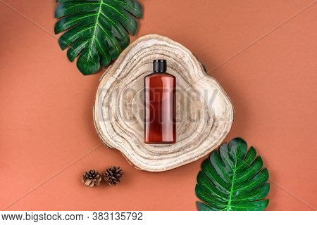 Brown Bottle Of Lotion, Cream, Shampoo On Wooden Cross Section Cut With Monstera Leaves On Brown Sur
