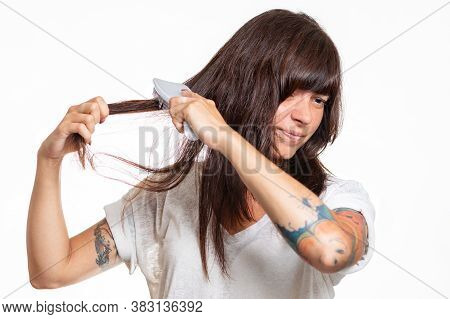 Portrait Of A Woman With Tattoos Combs A Lock Of Hair, Experiencing Pain And Pulling Out Her Hair. W