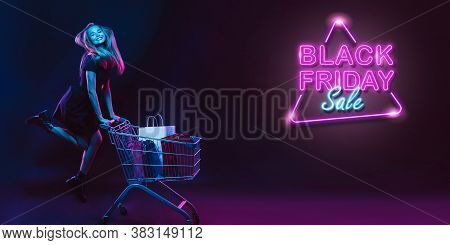 Flying High. Portrait Of Young Beautiful Woman In Neon Light On Dark Studio Backgound. Neoned Letter