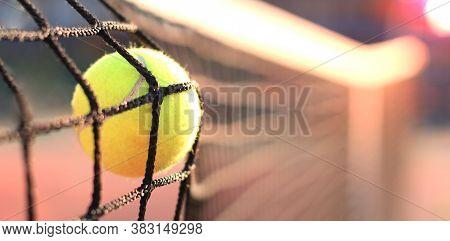 Bright Greenish Yellow Tennis Ball Hitting The Net.