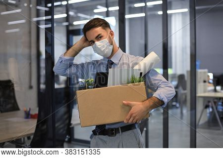 Dismissal Employee In An Epidemic Coronavirus. Dismissed Worker Going From The Office With His Offic