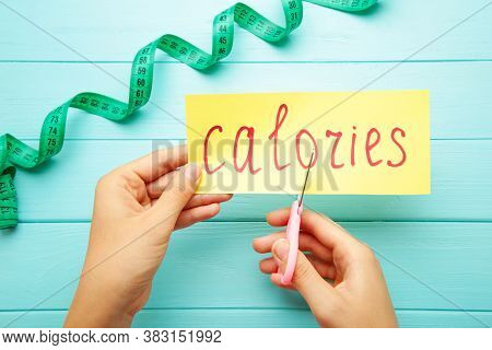 Woman Hand Holding Card With The Word Calories. Cutting Calories. Top View