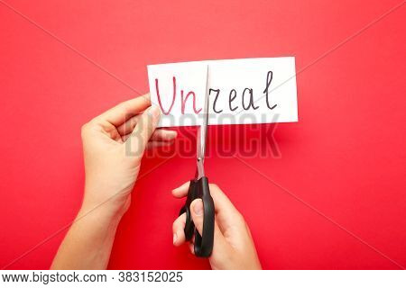 Paper With Word Unreal And Scissors On Wooden Table. Hand Holding Card With The Text Unreal. Top Vie