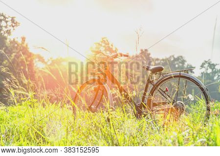 Blurred A Picture Of A Bicycle Parked In A Wide Field. Retro Concept, Beautiful Scenery With Bicycle