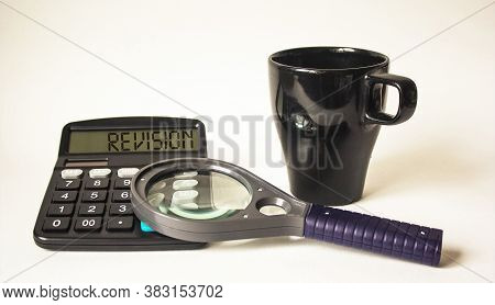 Revision Text Is Written On A Calculator, Next To A Black Cup And A Magnifying Glass On A White Back