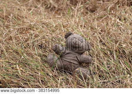 Old Dirty Teddy Bear Neglected On The Dry Grass Ground. End Of Childhood.