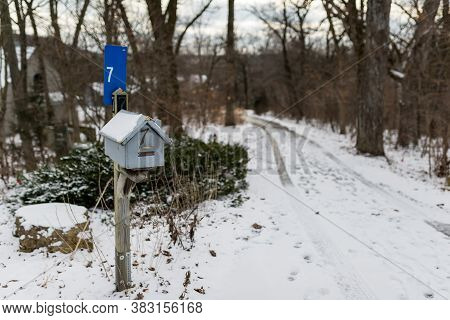 A House Shaped Wooden Mailbox Covered With Snow, Winter Scene
