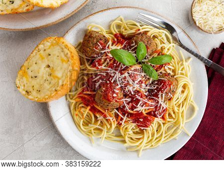 Overhead Of Spaghetti And Meatball Dinner With Toasted Cheese Bread On A Plate