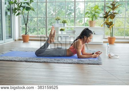 Training At Home.young Asian Woman Lying On Mat With Relaxing And Using Mobile Phone, While Break On