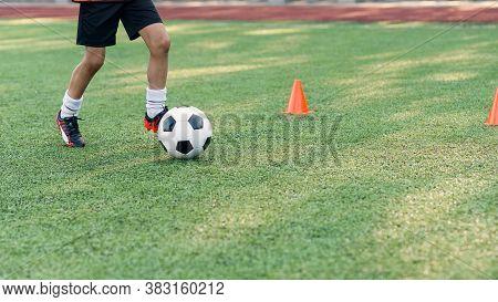 Soccer Player Kicking Ball On Field. Soccer Players On Training Session. Close Up Footballer Feet Ki