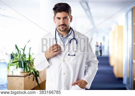 Shot Of Smiling Male Doctor Standing On The Hospital's Foyer.