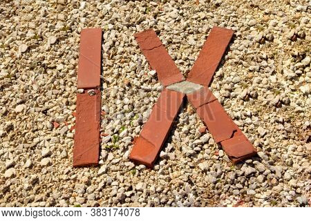 The Roman Numeral Nine Is Laid Out In Red Brick On Gravel.