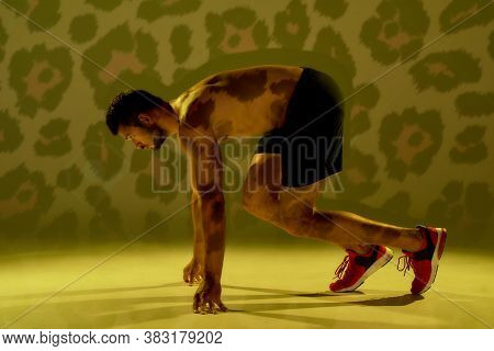 Run Like A Devil. Side View Of A Young Muscular Caucasian Man Standing In Start Position, Ready For