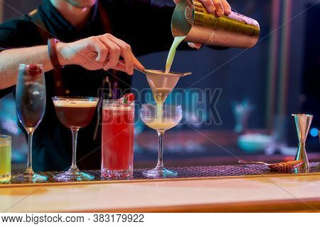 Best Alcohol Here. Close Up Of Hands Of Male Bartender Pouring, Mixing Ingredients While Making Cock