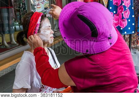 Unidentified Woman Gets A Traditional String Facial By A Beautician On The Sidewalk.