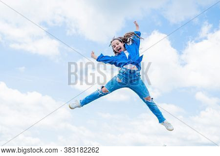 Smiling Child Jumping So High. Carefree And Joyful. Kid Fashion Style. Teenage Girl On Sky Backgroun