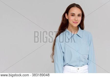 Close Up Portrait Of Smiling Young Woman In Blue Shirt Looking At Camera, Isolated On Gray Backgroun