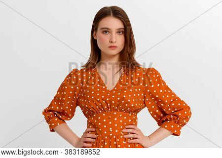 Beautiful Smiling Young Woman Is Holding Hands On Hip And Looking At Camera. Three Quarter Length St