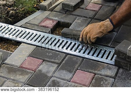 Installation Of Iron Drainage System And Paving Slabs. A Close-up Of An Iron Grating Along The Sidew